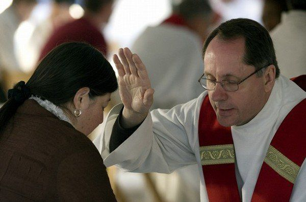 A priest gives confession to a woman at Nationals Park in Washington, DC, April 17, 2008, prior to mass with Pope Benedict XVI. Pope Benedict XVI will celebrate Catholic Mass for an audience of 45,000 people at the ballpark. AFP PHOTO/Jim WATSON (Photo credit should read JIM WATSON/AFP/Getty Images)