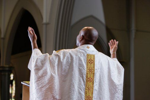 Priest praying in church, rear view