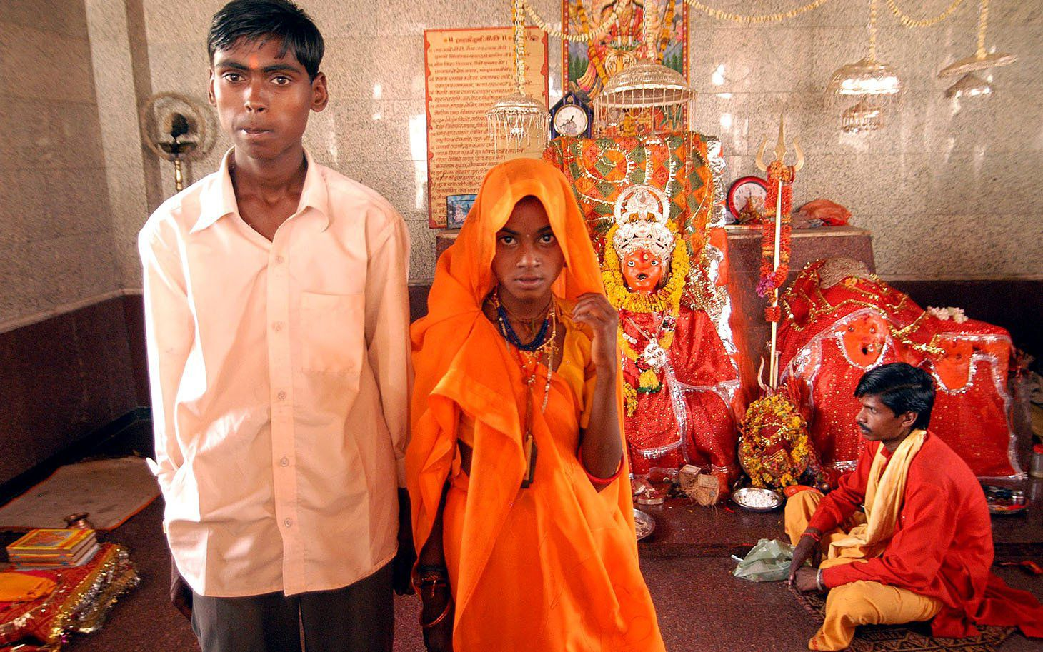 Eleven-year-old Anita, standing right, and her groom Birbal, 16, pose for a photograph after their marriage, as a priest looks on at Jalpa Mata temple in Rajgarh, about 155 kilometers (96 miles), northwest of Bhopal, India, Sunday, April, 30, 2006. Ignoring laws that ban child marriages, hundreds of children, some as young as seven years old, were married in a centuries-old custom across central and western India this week, according to news reports. (AP Photo/Prakash Hatvalne)