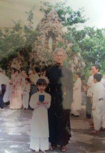 Thầy Giuse Võ Văn Tuệ chụp với một em thiếu nhi trong ngày Rước Lễ lần đầu. Ảnh chụp trước hang đá Đức Mẹ, nhà thờ Thái Hà.