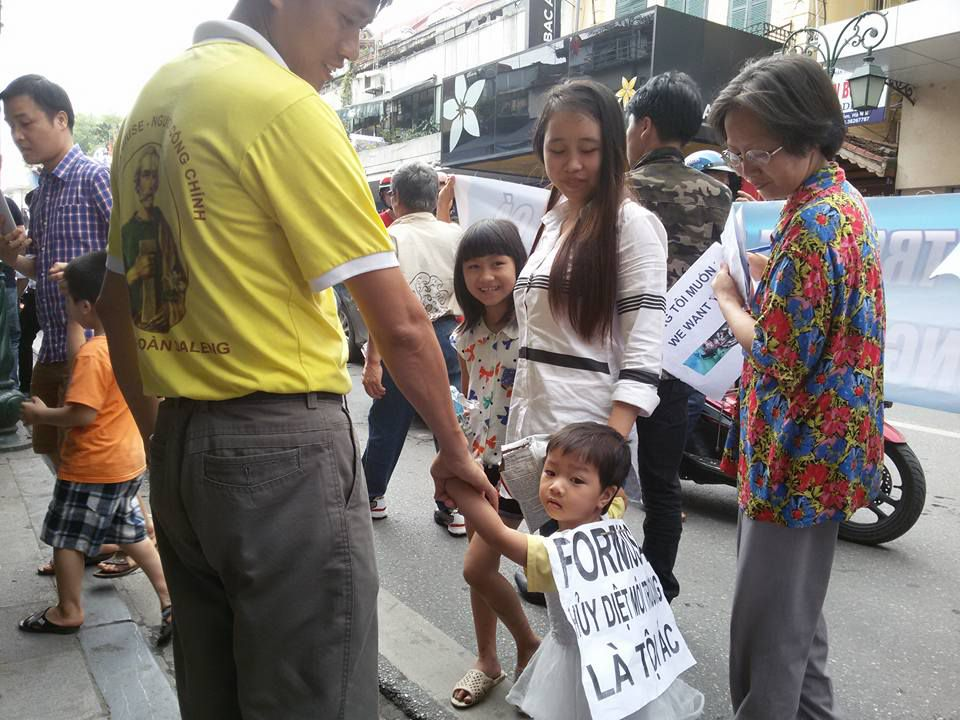 Đôi vợ chồng trẻ với hai đứa con chạy xe gắn máy mấy chục km để về Hà Nội tham gia cuộc xuống đường.