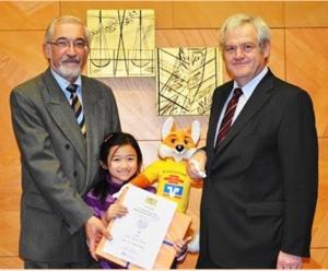 Ảnh chụp: Thanh Mai, lúc 8 tuổi, nhận chứng chỉ vô địch vòng thi chung kết toán lớp 4 toàn tỉnh Unterfranken, Đức, năm 2011