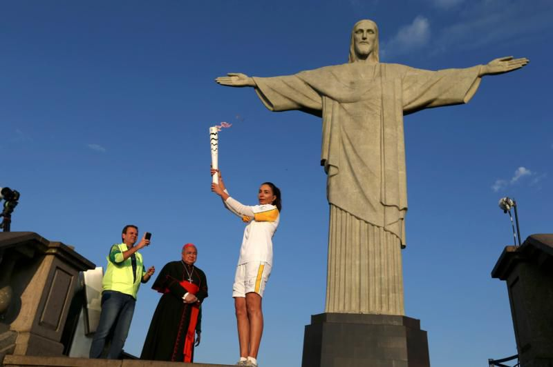 Former Brazilian volleyball player Isabel Barroso holds the Olympic torch Aug. 5 next to the Christ the Redeemer statue as Rio de Janeiro Mayor Eduardo Paes and Cardinal Orani Tempesta look on. (CNS photo/Pilar Olivares, Reuters) See OLYMPICS-TORCH-STATUE Aug. 5, 2016.