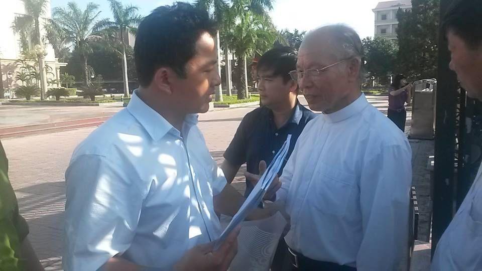 Linh mục Phê-rô Nguyễn Phúc Chính, quản xứ Cửa Sót (tay phải) đang trao đổi với một cán bộ tại khu vực  trước cổng UBND thành phố Hà Tĩnh