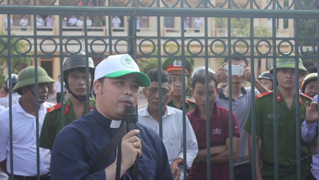 Linh mục Anton Đặng Hữu Nam nói chuyện với các ngư dân biểu tình bên ngoài trụ sở tòa án Hà Tĩnh, Việt Nam, ngày 26/09/2016