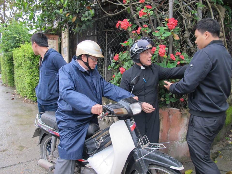 Lm. Trần Văn Quý và Phan Văn Lợi bị hai viên an ninh ngăn cản không cho tới địa điểm dâng lễ. Ảnh FB Phan Văn Lợi