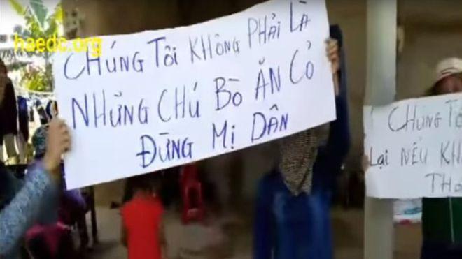 Người biểu tình giơ cao biểu ngữ trước cửa nhà trưởng thôn Cồn Sẻ - hình từ video clip đăng trên YouTube