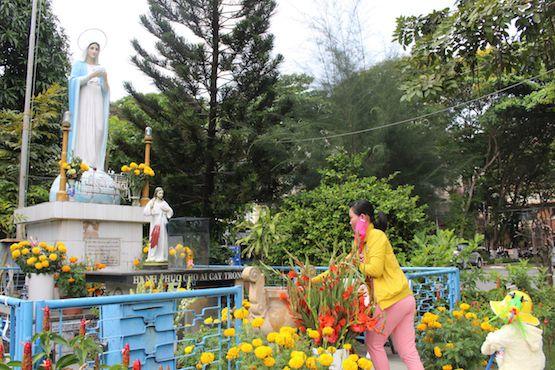 Một phụ nữ dâng hương trước tượng Đức Mẹ trong bệnh viện Bệnh Nhiệt đới ở Sài Gòn. Ảnh: ucanews.com