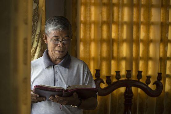 Mục sư Sok Sophon đọc Kinh thánh giữa phòng họp của Hội Truyền giáo Phúc âm liên hiệp của Campuchia ở ngoại ô Phnôm Pênh (Ảnh: Enric Catala Contreras)