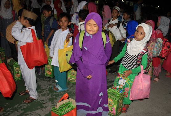 Các trẻ em Hồi giáo nhận quà từ các tình nguyện viên Công giáo sau bữa ăn sáng Eid al-Fitr tại Trường Tiểu học St Maria ở Jakarta, ngày 19 tháng 6 năm 2017 (ảnh ucanews.com)